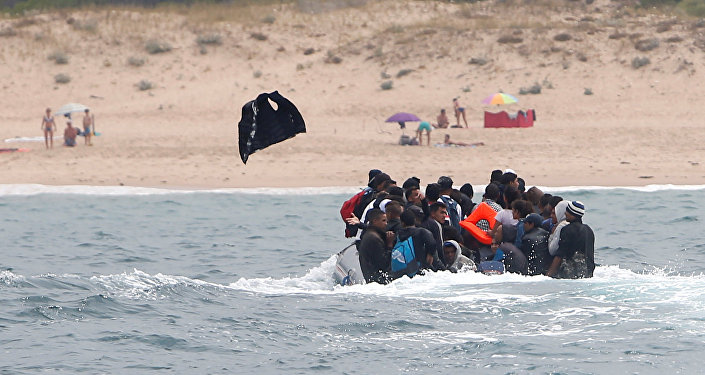 Migrants throws up a life-vest before disembarking from a dinghy at Del Canuelo beach after they crossed the Strait of Gibraltar sailing from the coast of Morocco, in Tarifa, southern Spain, July 27, 2018