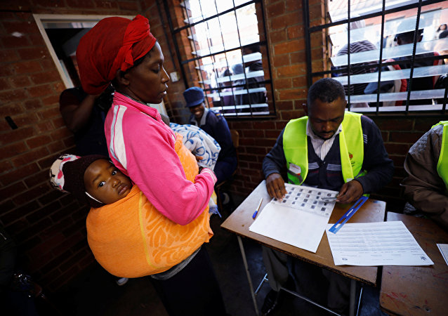 A Zimbabwean voter registers to cast her ballot in the country's general elections in Harare, Zimbabwe, July 30, 2018