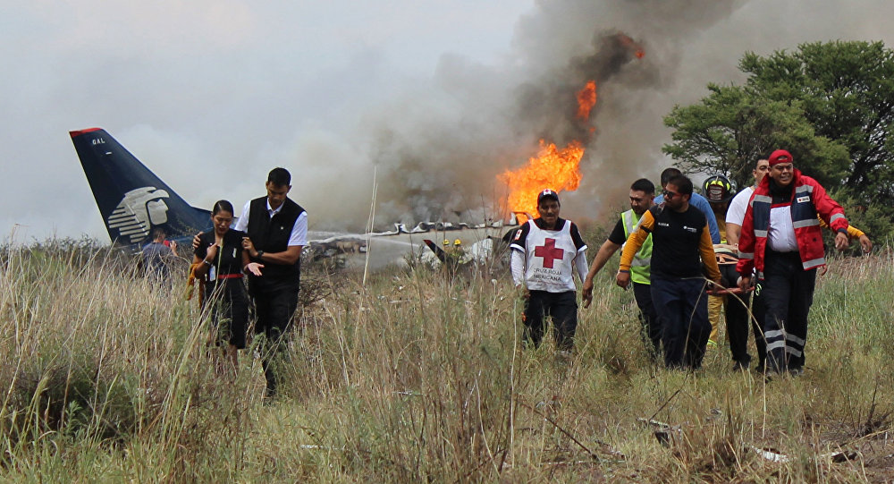 In this photo released by Red Cross Durango communications office, Red Cross workers and rescue workers carry an injured person on a stretcher, right, as airline workers, left, walk away from the site where an Aeromexico airliner crashed in a field near the airport in Durango, Mexico, Tuesday, July 31, 2018