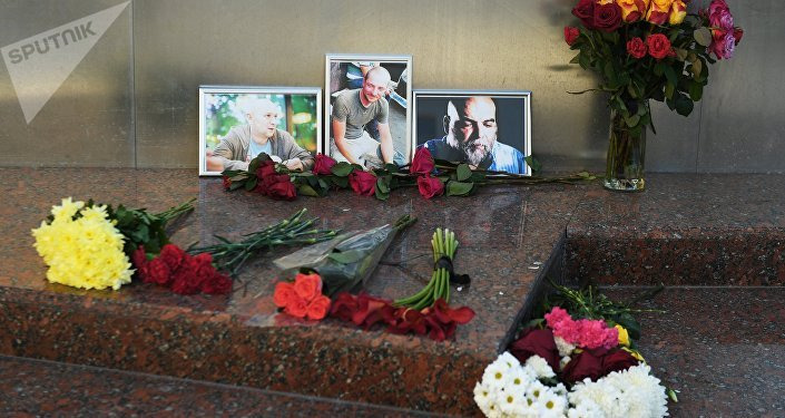 Flowers brought at the photos of three Russian journalists killed in the Central African Republic, from right: Orkhan Dzhemal, Kirill Radchenko and Alexander Rastorguyev, near the Central House of Journalists in Moscow. File photo
