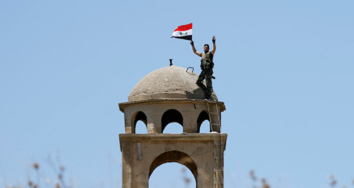 A Syrian army soldier gestures as he holds a Syrian flag in Quneitra, Syria July 27, 2018