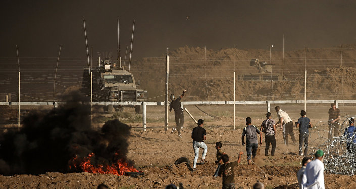 Palestinian protesters throw stones towards Israeli forces during a demonstration along the border between Israel and the Gaza strip, east of Gaza city on July 27, 2018