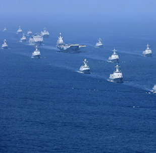 In this April 12, 2018 photo released by Xinhua News Agency, the Liaoning aircraft carrier is accompanied by navy frigates and submarines conducting an exercises in the South China Sea