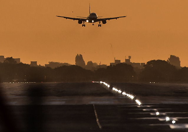 A passenger aircraft prepares to land during sunrise at London Heathrow Airport in west London on October 17, 2016
