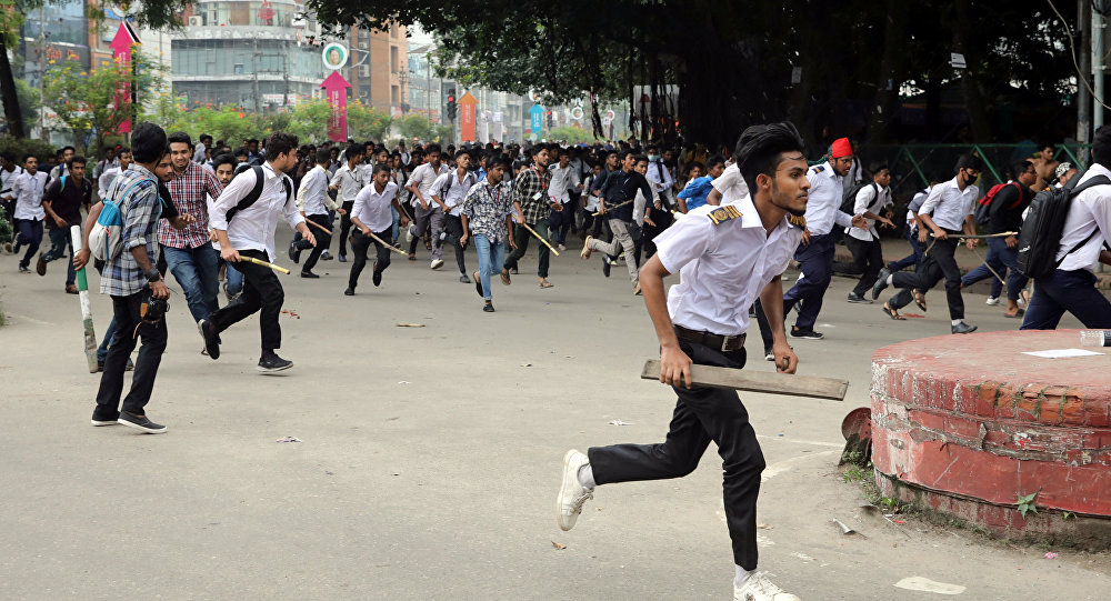 Students runs back during clashes with unidentified miscreants while protesting over recent traffic accidents that killed a boy and a girl, in Dhaka, Bangladesh, August 4, 2018