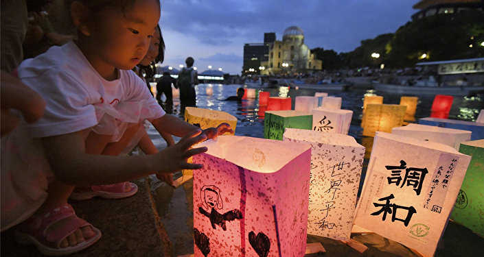 A girl releases paper lanterns on the Motoyasu river facing the gutted Atomic Bomb Dome in remembrance of atomic bomb victims on the 73rd anniversary of the bombing of Hiroshima, western Japan, August 6, 2018