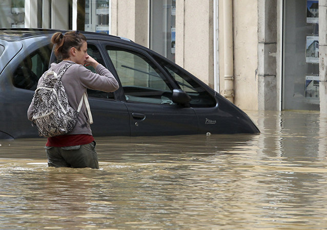 A woman walks on a flooded street caused by heavy rain and thunder storms, in Salies-de-Bearn, southwestern France, Wednesday, June 13, 2018