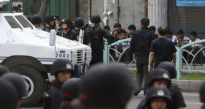 Uyghur protesters, sitting, are detained by security force officers after they marched to protest through the street in Urumqi, western China's Xinjiang province (File)
