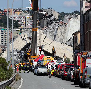 Firefighters and rescue workers stand at the site of a collapsed Morandi Bridge in the port city of Genoa, Italy August 15, 2018