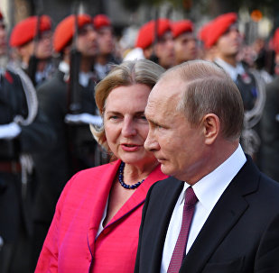 Russian President Vladimir Putin (R) and Austrian Foreign Minister Karin Kneissl take part in a wreath laying cermony at the Soviet World War II memorial in Vienna, Austria, June 5, 2018