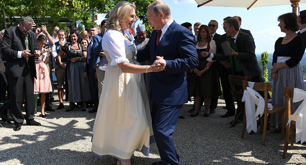 Russian President Vladimir Putin, right, congratulates Austrian Foreign Minister Karin Kneissl as he attends the wedding of Kneissl with with Austrian businessman Wolfgang Meilinger in Gamlitz, southern Austria, Saturday, Aug. 18, 2018.