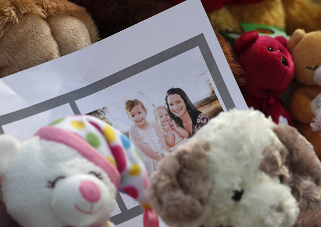 A photograph sits amid the tributes as they grow outside the home where a pregnant woman, Shanann Watts, and her two daughters, Bella and Celeste, lived Thursday, Aug. 16, 2018, in Frederick, Colo.