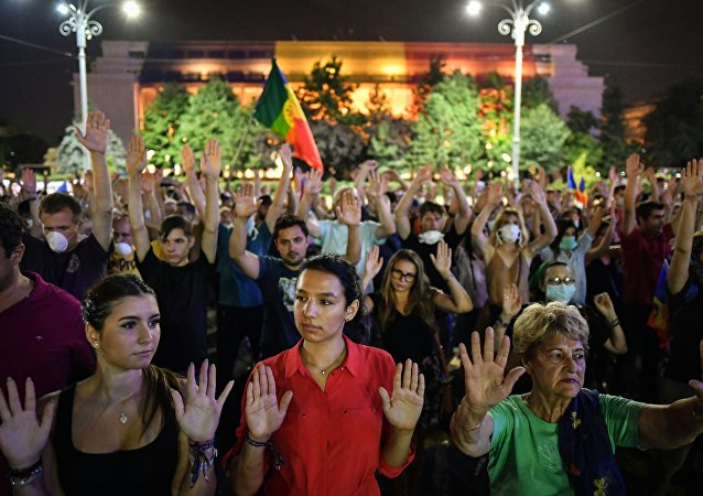 People raise their hands during a protest in front of the Romanian Government headquarters in Bucharest on August 17, 2018