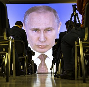 In this file photo taken Thursday, March 1, 2018, journalists watch as Russian President Vladimir Putin gives his annual state of the nation address in Manezh in Moscow, Russia. Buoyed by an oil boom, President Vladimir Putin's rule since 2000 has been marked by complaints about corruption and human rights abuse, tension with the West over Moscow's 2014 annexation of Crimea and accusations of meddling in U.S. elections