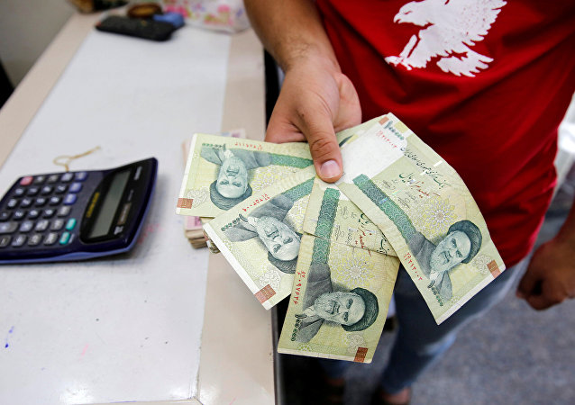 A vendor inspects Iranian rials at a currency exchange shop in Baghdad, Iraq August 8, 2018