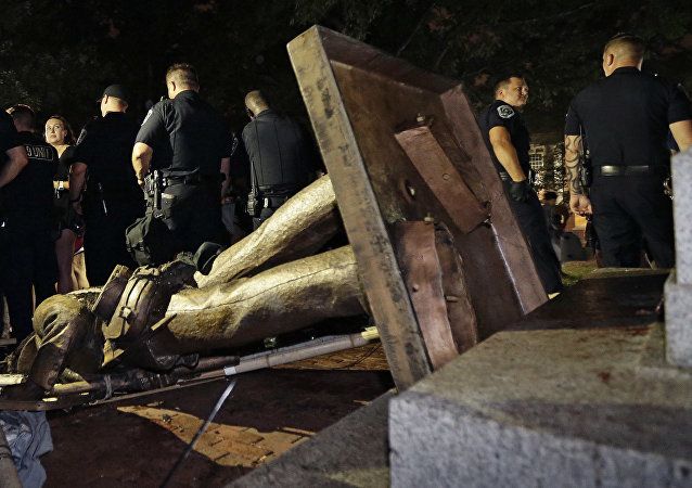 Police stand guard after the confederate statue known as Silent Sam was toppled by protesters on campus at the University of North Carolina in Chapel Hill, N.C., Monday, Aug. 20, 2018