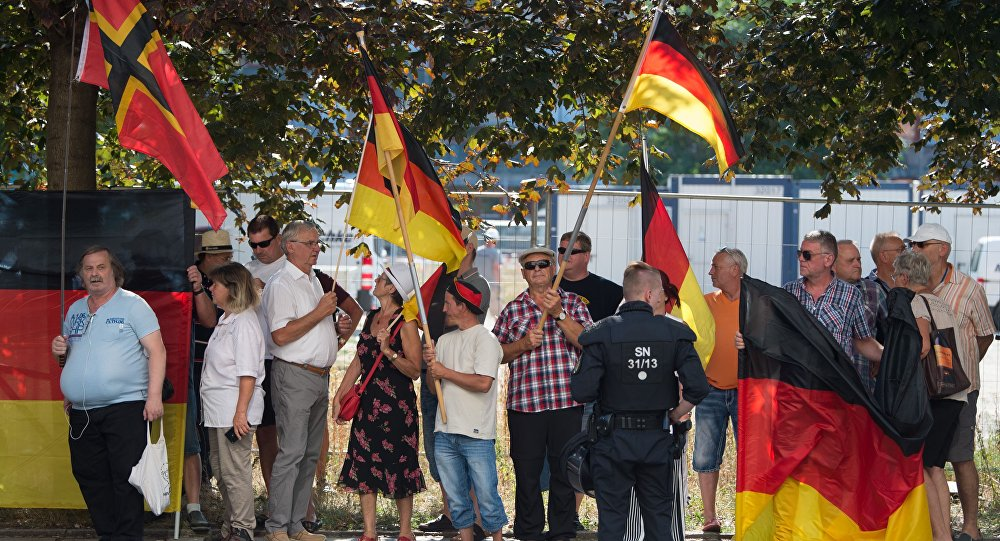 This picture taken on August 16, 2018 in Dresden, eastern Germany, shows anti-Islam Pegida movement supporters demonstrating on the occasion of German Chancellor's visit at the Saxon state parliament