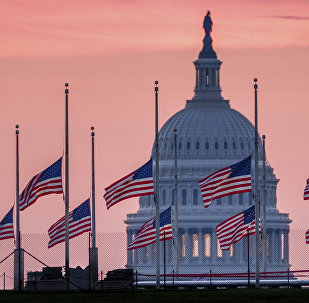 Flags flying a half-staff in honor of Sen. John McCain, R-Ariz., frame the U.S. Capital at daybreak in Washington, Sunday, Aug. 26, 2018.
