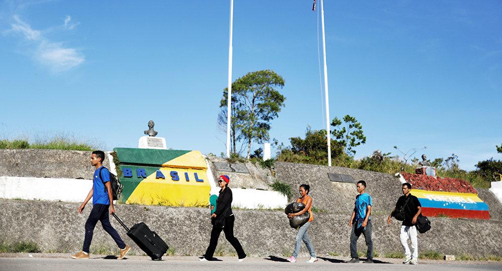 Venezuelans walk across the border from Venezuela into the Brazilian city of Pacaraima