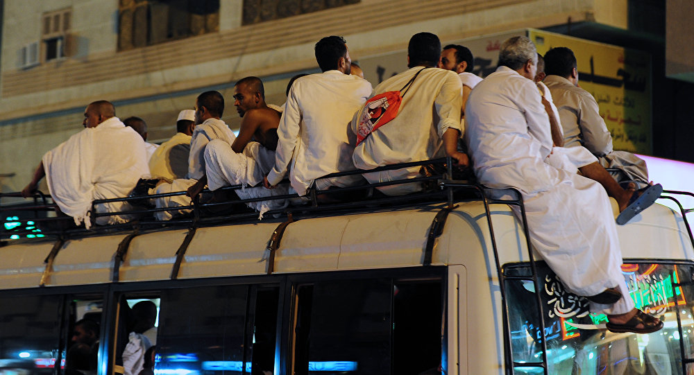 Muslim pilgrims sit on top of a bus heading to the Grand Mosque in Mecca (File)
