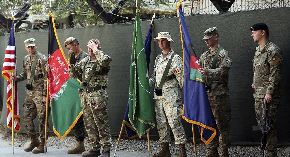 Afghanistan and NATO soldiers hold their flags before the start of the change of command ceremony at Resolute Support headquarters, in Kabul, Afghanistan, Sunday, Sept. 2, 2018