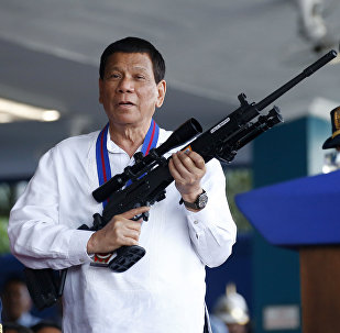 April 19, 2018 file photo, Philippine President Rodrigo Duterte, right, jokes to photographers as he holds an Israeli-made Galil rifle which was presented to him by former Philippine National Police Chief Director General Ronald Bato Dela Rosa at the turnover-of-command ceremony at the Camp Crame in Quezon city northeast of Manila