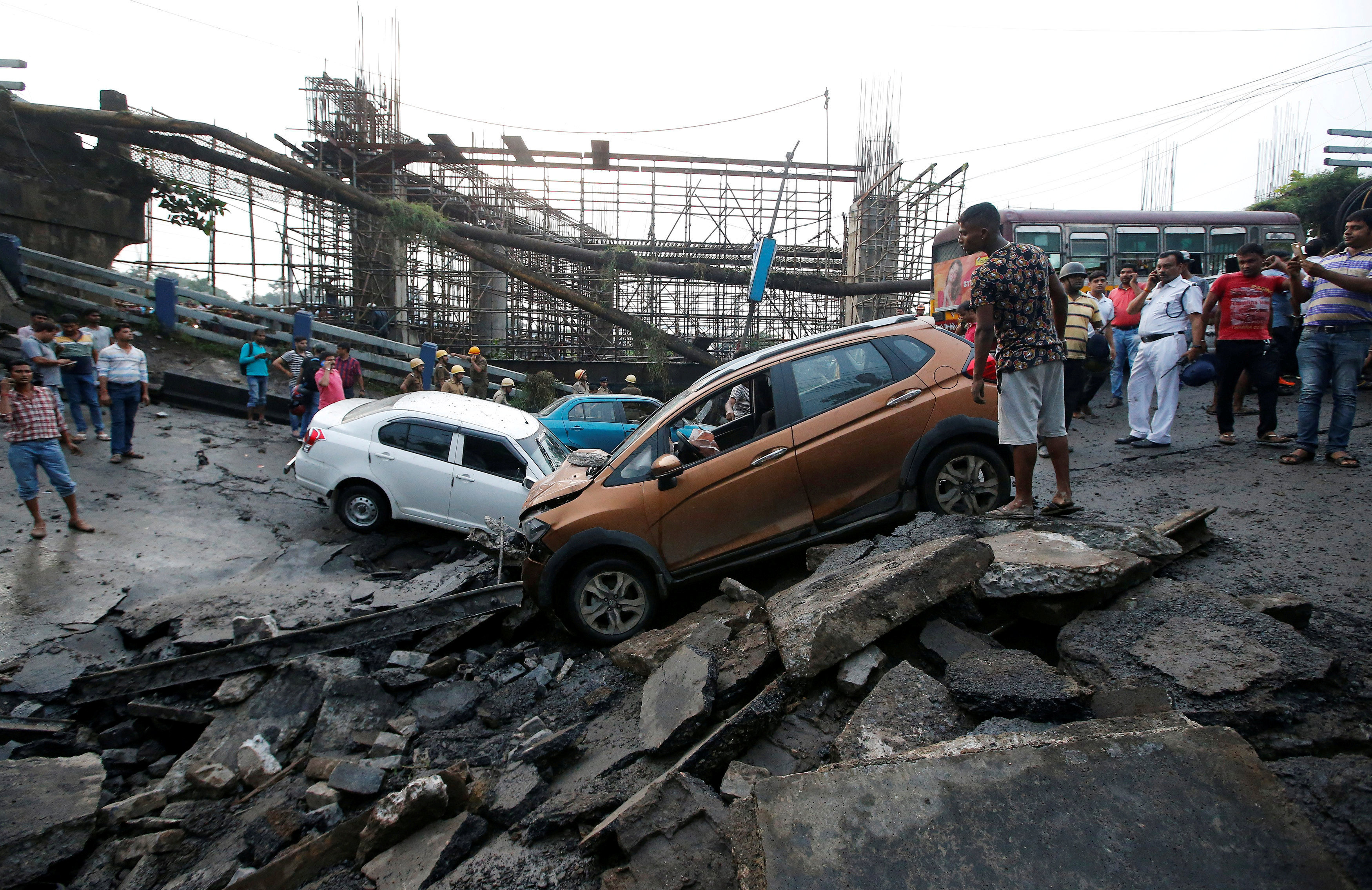 People stand next to the wreckage of vehicles at the site of a bridge that collapsed in Kolkata, India September 4, 2018.