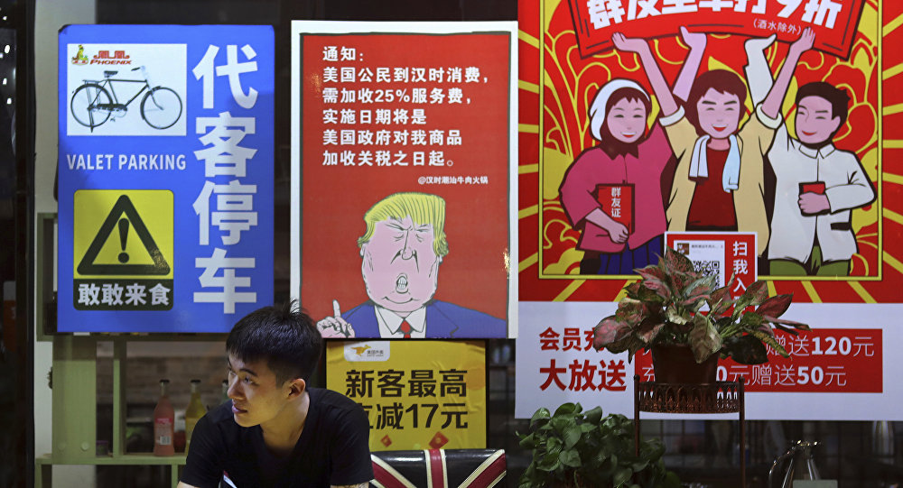 In this Monday, Aug. 13, 2018, photo, a man stands near a poster depicting a mural of U.S. President Donald Trump stating that all American costumers will be charged 25 percent more than others starting from the day president Trump started the trade war against China, on display outside a restaurant in Guangzhou in south China's Guangdong province. The recent trade war between the world's two biggest economies has forced many multinational companies to reschedule purchases and rethink where they buy materials and parts to try to dodge or blunt the effects of tit-for-tat tariffs between Washington and Beijing