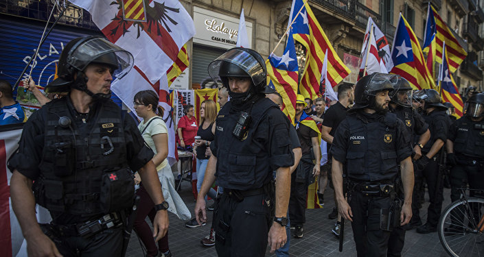 Members of a ultra-right-wing movement called 'Catalan Identitarian Movement' walk guarded by the police during celebrations of the Catalonia's regional holiday known as La Diada in Barcelona, Spain, Tuesday, Sept. 11, 2018