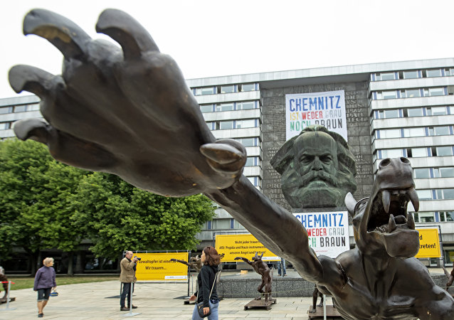 People walk between sculptures by artist Rainer Opolka in front of the Karl Marx Monument in Chemnitz, eastern Germany, Thursday, Sept. 13, 2018. The figure in the foreground is one of 10 life-sized metal wolf sculptures as a part of the spontan exhibition 'Wolves with Hitler salute howl in front of the Karl-Marx-Monument', to protest against xenophobia and right-wing extremism.