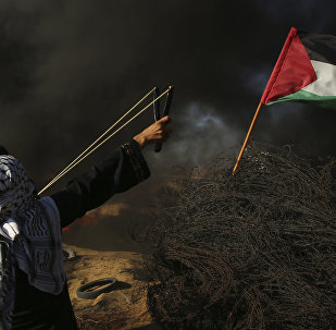 A female protester hurls a stone while others burn tires near the fence of the Gaza Strip border with Israel, during a protest east of Khan Younis, southern Gaza Strip, Friday, Aug. 10, 2018. Violence erupted at the Gaza border Friday after the territory's militant Islamic Hamas rulers and Israel appeared to be honoring a cease-fire that ended two days of intense violence amid efforts by neighboring Egypt to negotiate between the two sides