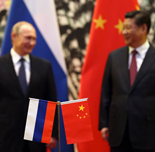 The Russian and Chinese national flags are seen on the table as Russia's President Vladimir Putin (back L) and his China's President Xi Jinping (back R) stand during a signing ceremony at the Diaoyutai State Guesthouse in Beijing on November 9, 2014.