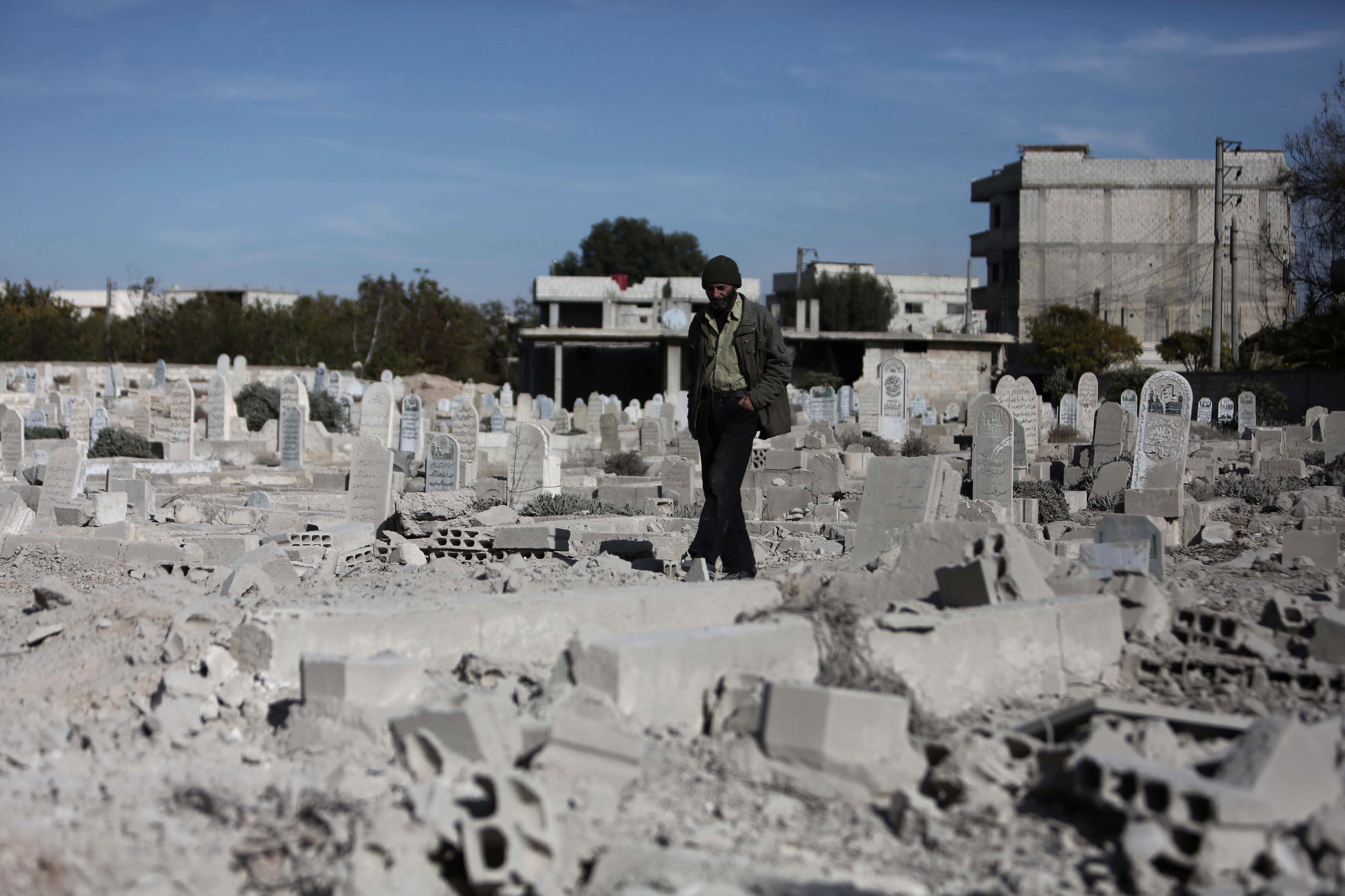 A man walks in a graveyard near destroyed graves in a neighbourhood heavily damaged by air strikes in the village of Deir al-Asafir in the rebel-held region of Eastern Ghouta, on the outskirts of the Syrian capital Damascus (File)