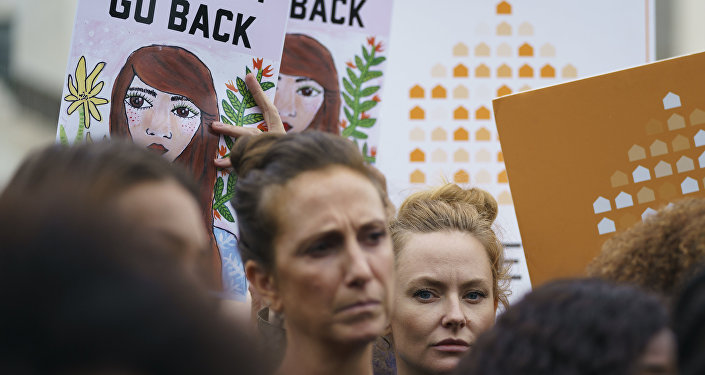 Protesters with Women's March and others hold up signs that read We Won't Go Back as they gather in front of the Supreme Court on Capitol Hill in Washington, Monday, Sept. 24, 2018.