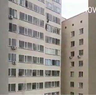 28-year-old Astana man Artem Yarev reaches for a seven-year-old boy dangling from the apartment window above him in Kazakhstan's capital, Sept 24, 2018