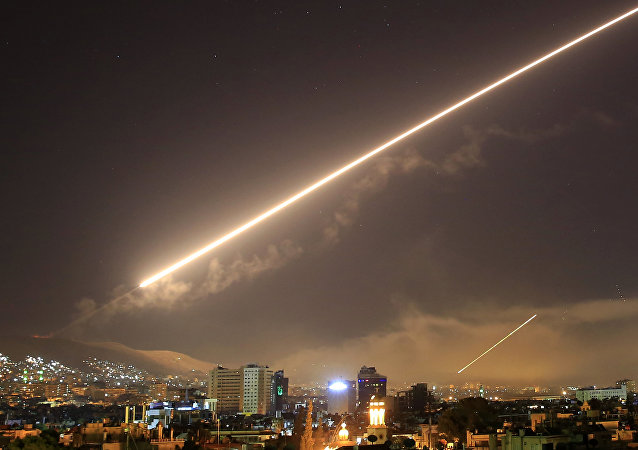 In this April 14, 2018 file photo, Damascus skies erupt with surface to air missile fire as the U.S. launches an attack on Syria targeting different parts of the Syrian capital Damascus, Syria