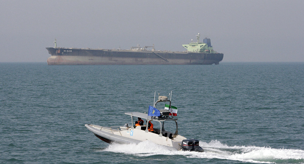 In this July 2, 2012 file photo, an Iranian Revolutionary Guard speedboat moves in the Persian Gulf while an oil tanker is seen in background