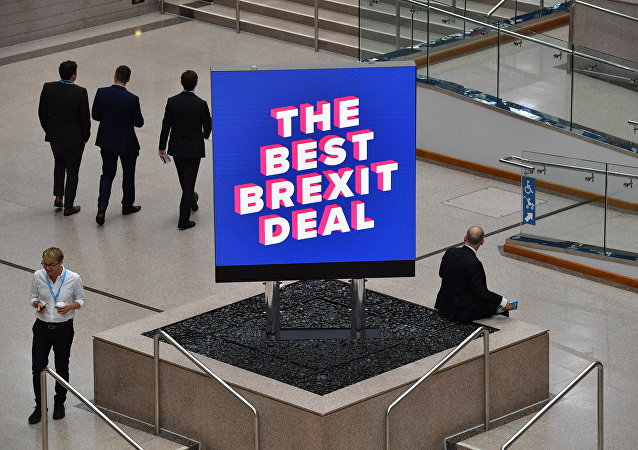 Delegates are seen near a sign that reads The Best Brexit Deal at the venue on the first day of the Conservative Party Conference 2018 at the International Convention Centre in Birmingham, on September 30, 2018.