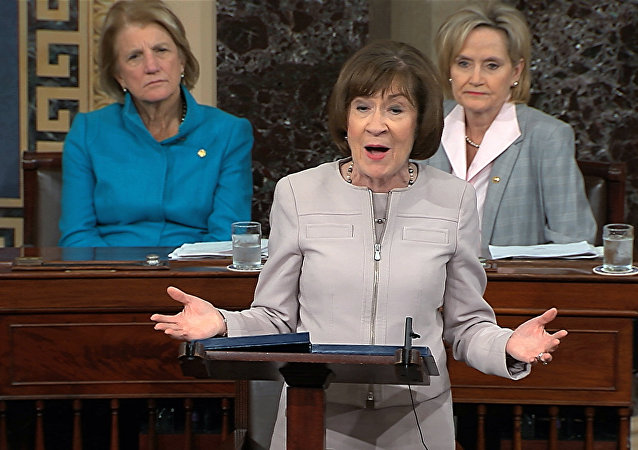 Sen. Susan Collins, R-Maine., speaks on the Senate floor about her vote on Supreme Court nominee Judge Brett Kananaugh, Friday, Oct. 5, 2018 in the Capitol in Washington. Sen Shelly Capito, R-W.Va., sits rear left and Sen. Cindy Hyde-Smith, R-Miss., sits right. (Senate TV via AP)