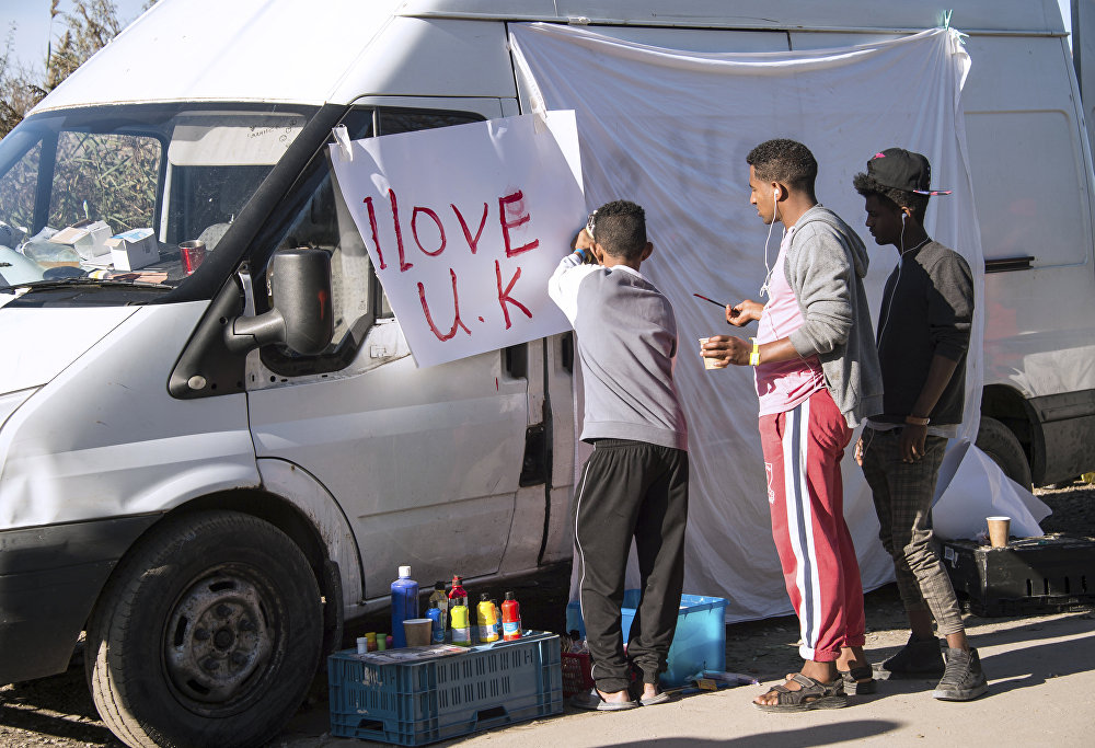 Young migrants paint a sheet of paper with the lettering 'I love UK' in the 'Jungle' migrant camp, in Calais, northern France, on October 31, 2016, during a massive operation to clear the squalid settlement where 6,000-8,000 people have been living in dire conditions.
