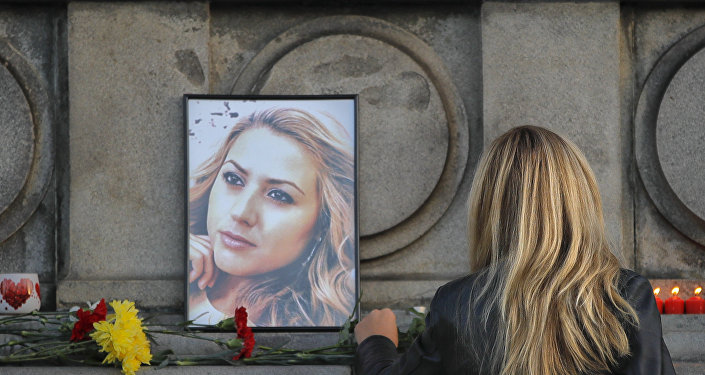 A woman places flowers next to a portrait of slain television reporter Viktoria Marinova during a vigil at the Liberty Monument in Ruse, Bulgaria, Monday, Oct. 8, 2018