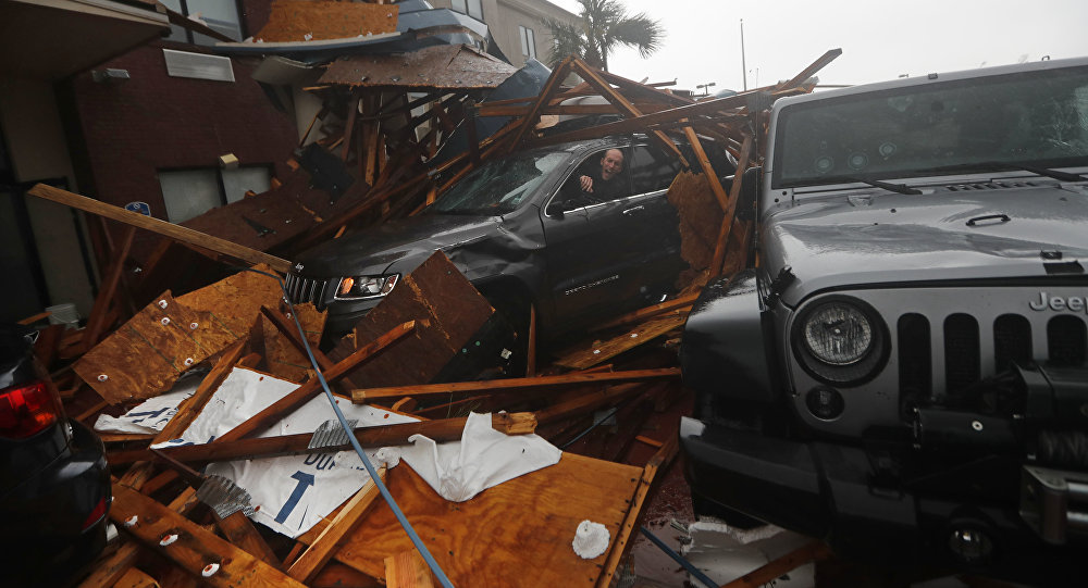 A storm chaser climbs into his vehicle during the eye of Hurricane Michael to retrieve equipment after a hotel canopy collapsed in Panama City Beach, Fla., Wednesday, Oct. 10, 2018