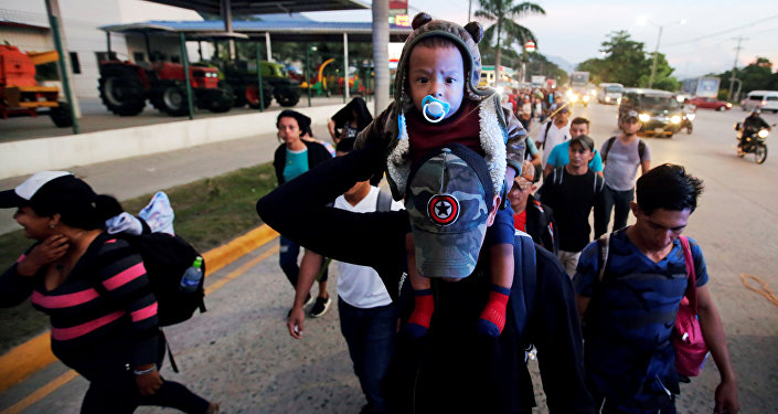 A man carries a child as they move in a caravan toward the United States, in San Pedro Sula, Honduras October 13, 2018