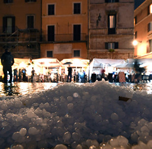 Hail covers the street in downtown Rome during a hailstorm on October 21, 2018