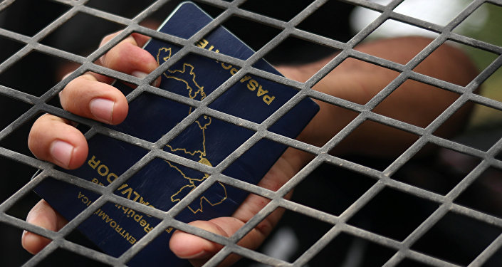 A man from El Salvador holds his passport in the back of a U.S. border patrol vehicle after he is apprehended for illegally crossing into the United States from Mexico in La Joya, Texas, U.S., October 17, 2018
