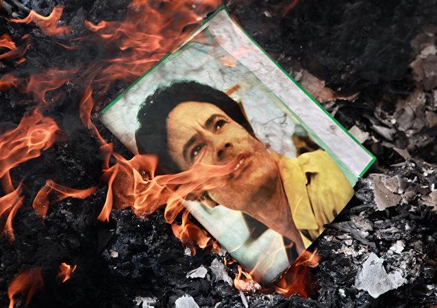 A portrait of Muammar Gaddafi burning in a fire.