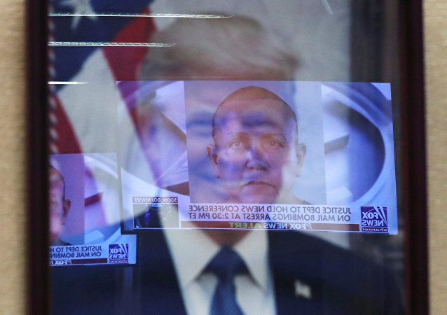 Televised pictures of parcel bombs suspect Cesar Sayoc are reflected in the official portrait of US President Donald Trump at the Justice Department in Washington DC, October 26, 2018
