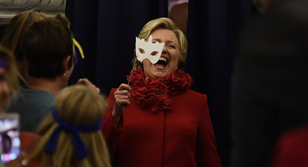 US Democratic presidential nominee Hillary Clinton smiles holding a mask onboard her campaign plane Erlanger, Kentucky, on October 31, 2016