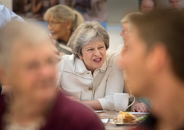 Britain's Prime Minister Theresa May reacts as she talks with people attending a social group in Vauxhall, south London, on October 15, 2018, where she launched the government's loneliness strategy