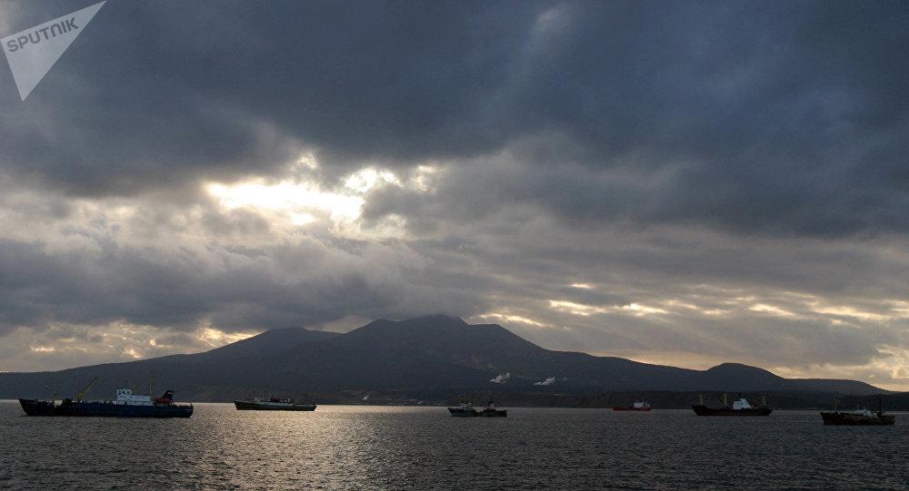 Kunashir Island, Kuril Islands. Russian fishing vessels in the foreground